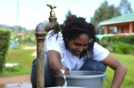 Jacinda Small rewashes sand using water from a tank.